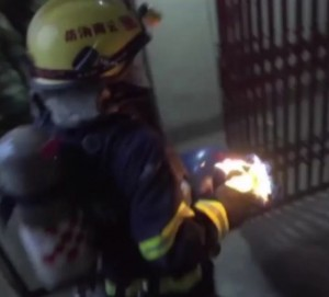 FIREFIGHTER REMOVES BURNING GAS CONTAINER FROM STRUCTURE